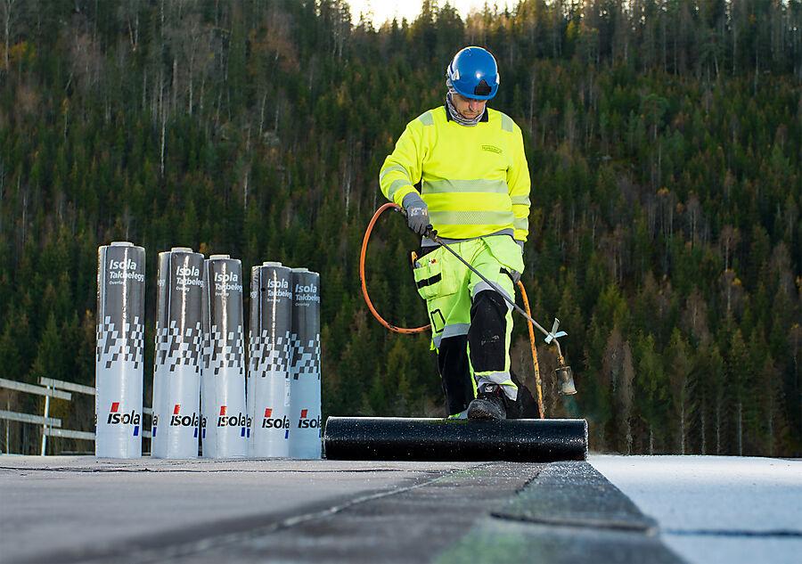 Taktekker sveiser Isola Mestertekk Kombi på flatt tak, bak står flere ruller